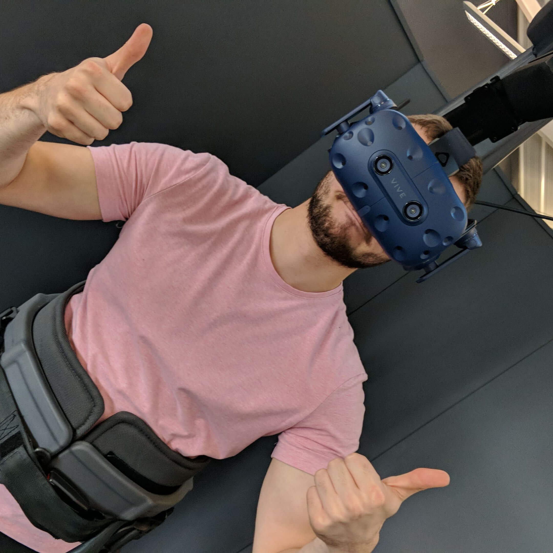 Male worker wearing virtual reality smart glasses with thumbs up