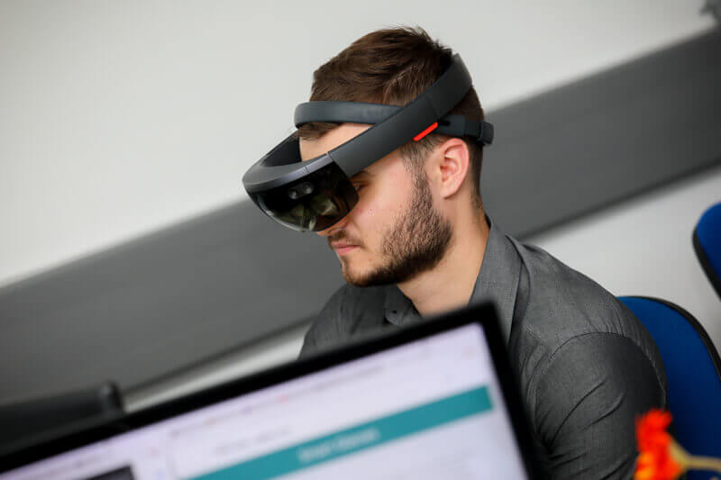 Man at desk with virtual reality smart glasses